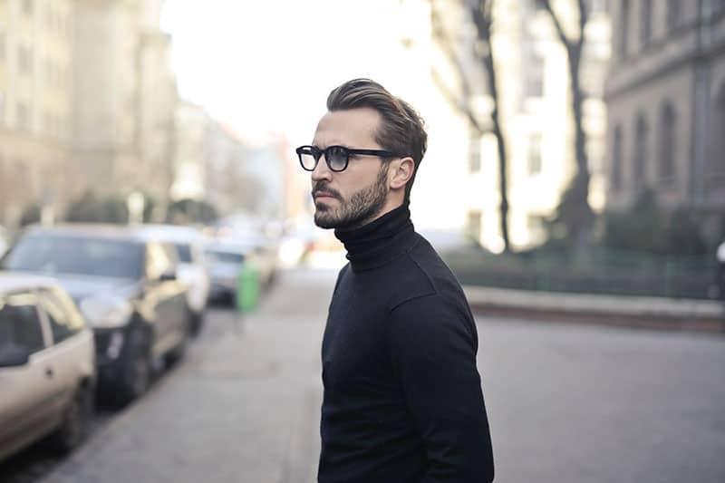 man wearing eyeglasses and black sweatshirt standing outside