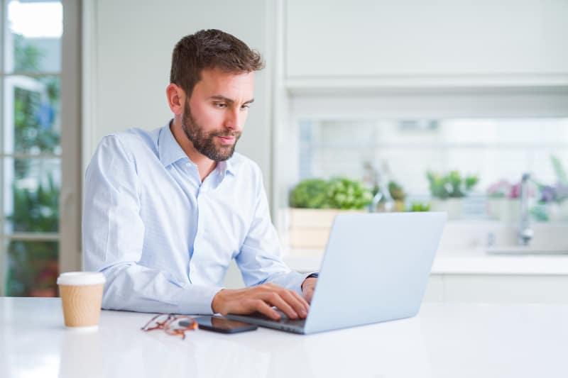 man wearing shirt typing on laptop