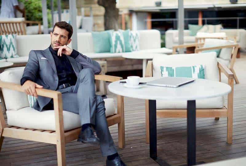 man wearing suit and sitting in outdoor cafe
