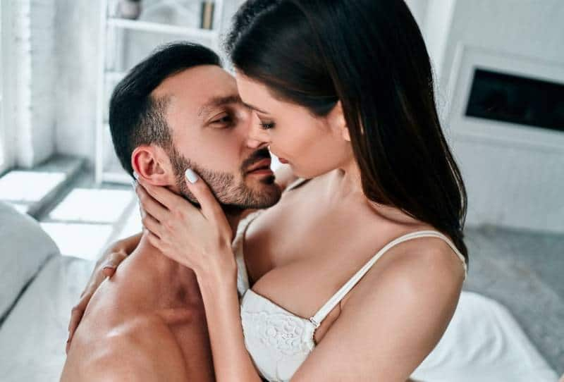 passionate couple kissing in bedroom