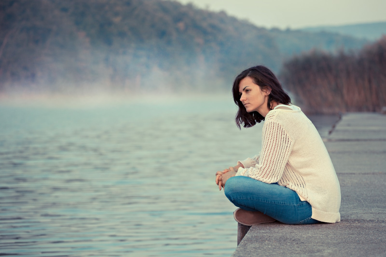 pensive woman sitting by the lake