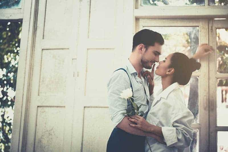 romantic couple about to kiss while woman holding white rose