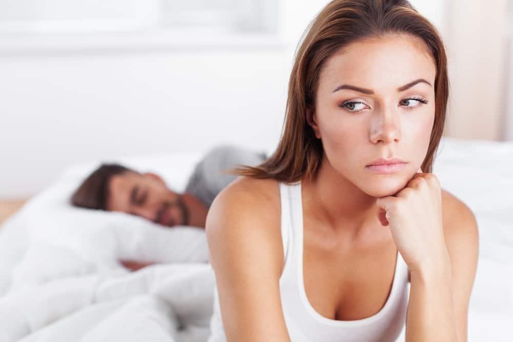 sad woman sitting on bed while man sleeping