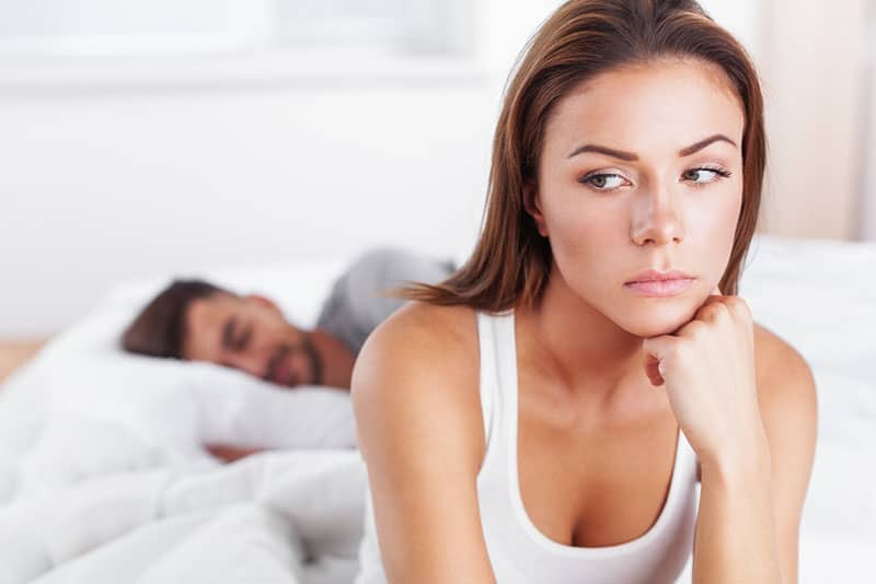 sad woman sitting on bed while man sleeping
