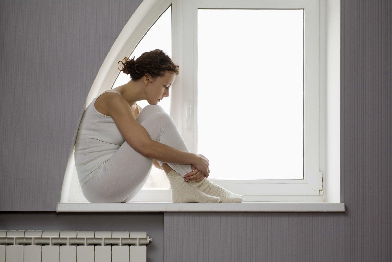 sad woman sitting on window sill
