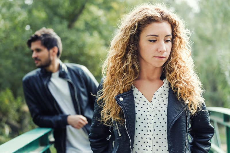 sad woman standing in front of her boyfriend