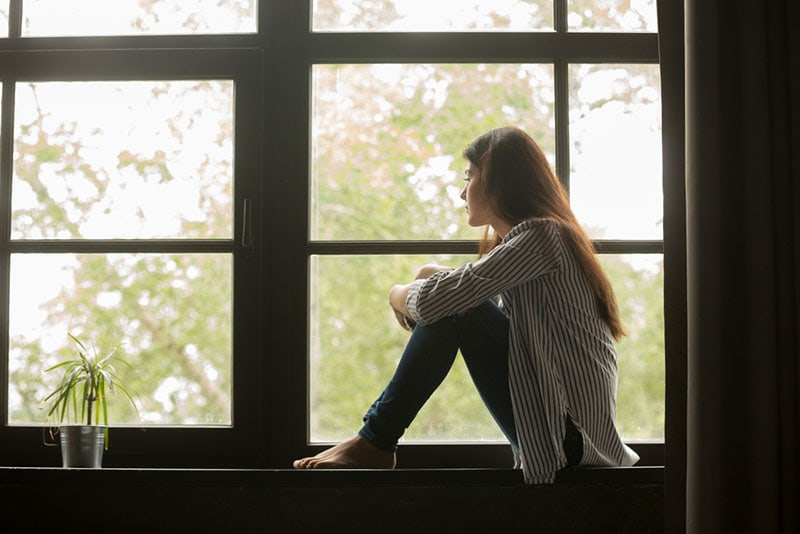 sad young woman sitting by window