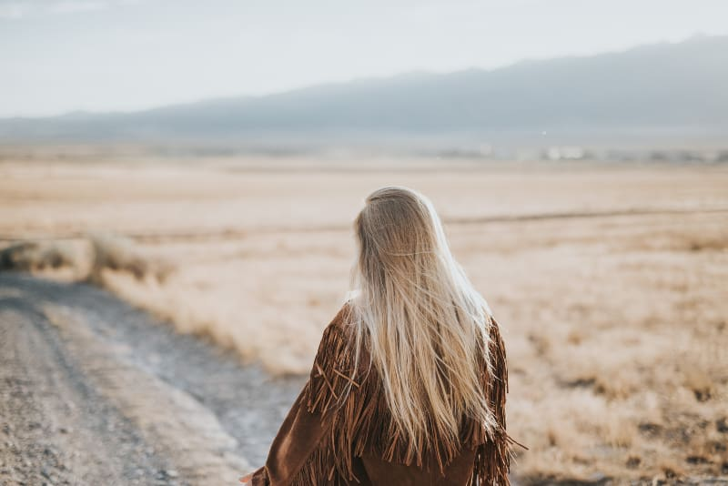 girl with long blonde hair walking in nature