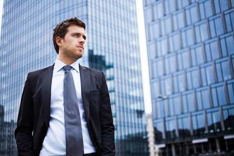 serious man in suit standing beside buildings