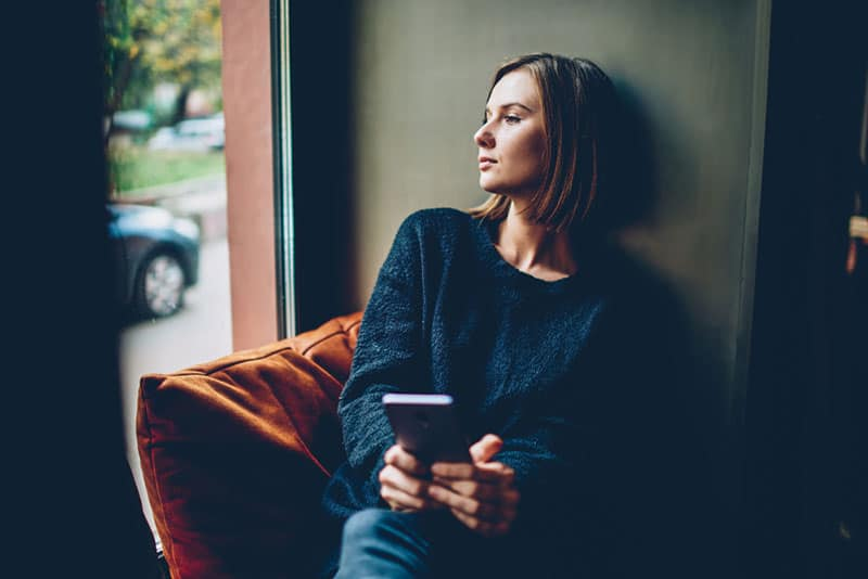 Thoughtful young woman dressed in black casual outfit looking out of window resting in comfortable coworking space. Pondering hipster girl with smartphone in hands thinking on future