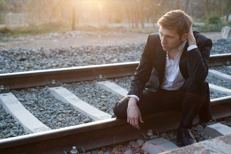 Portrait of young man with suit sitting in rail way