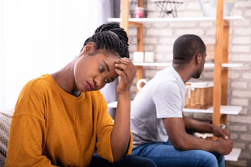Upset Young African Couple Sitting On Sofa Ignoring Each Other