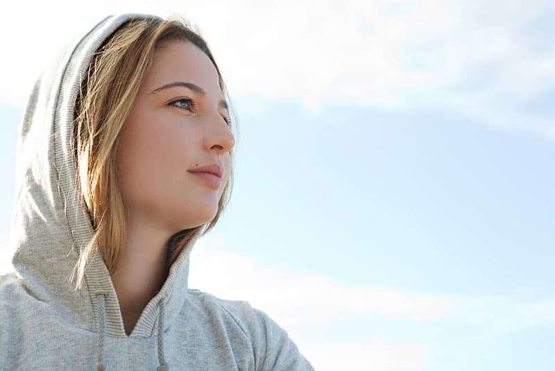 Close up portrait of a beautiful young sports woman wearing a hood during a sunny morning against a blue sky