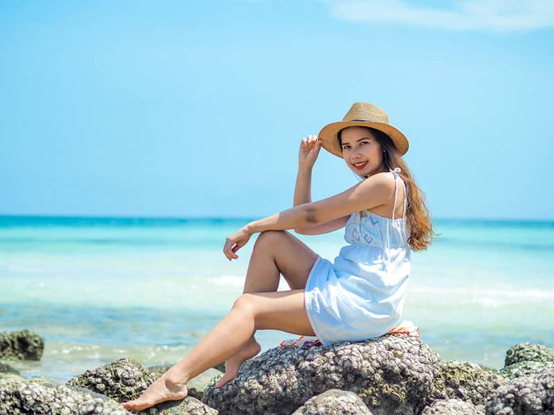 Happy young asian woman enjoy summer vacation on the beach.