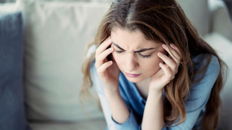 Young woman with headache in home
