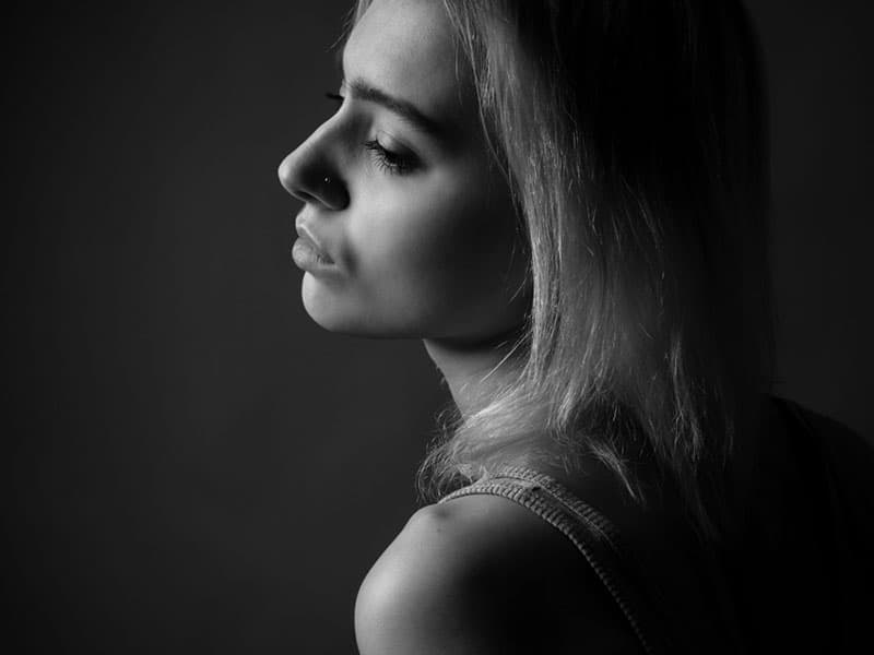 Portrait of girl in studio. Black and white. Profile.