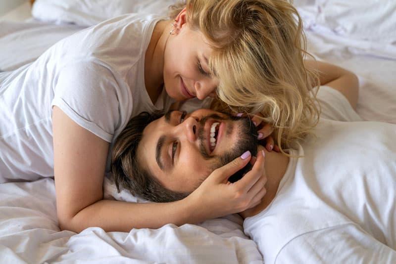 Happy couple in love having fun in bedroom stock photo