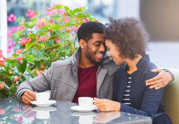 African young couple in love sitting at cafe, hugging and drinking coffee, empty space