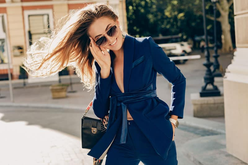 attractive smiling woman with long hair walking on sunny weather in autumn city wearing sexy blue suit, street fashion style