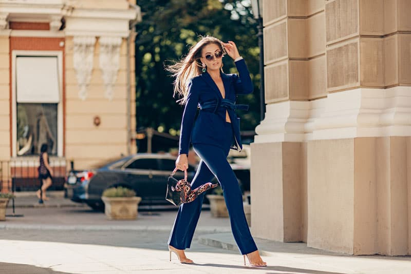 luxury rich woman dressed in elegant stylish blue suit walking in city on sunny autumn day holding purse, fashion trend