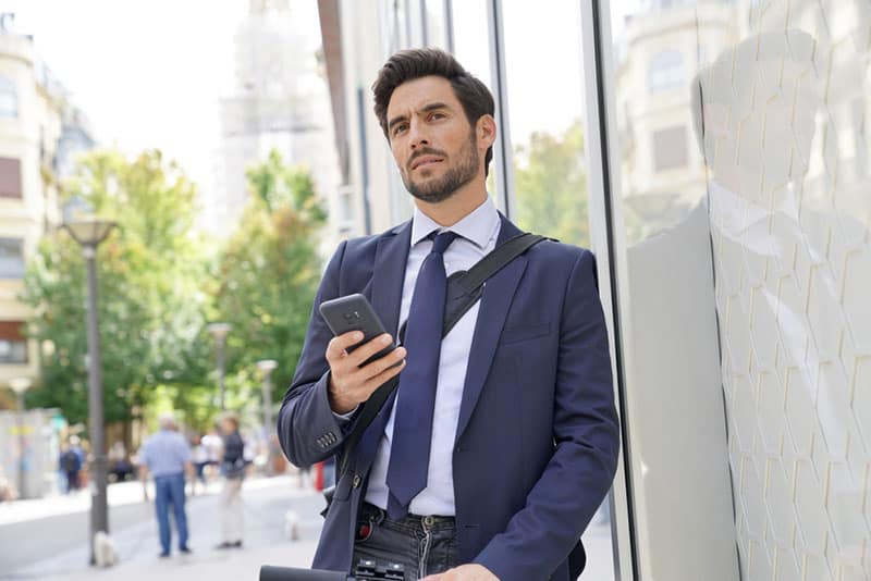 Businessman in the street using smartphone and electric scooter