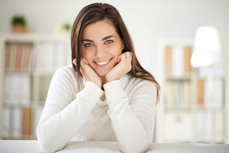 Happy girl in white pullover looking at camera with smile