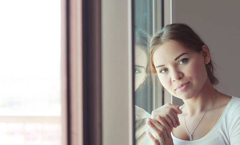 beautiful woman stands in front of the window