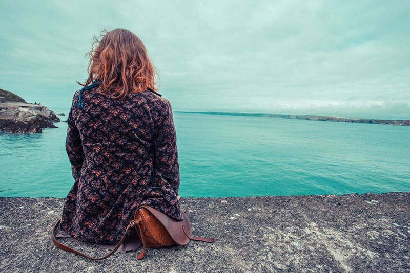 A young woman is sitting by the water's edge in a harbour