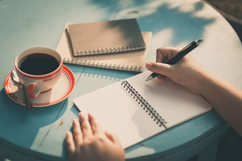 Woman right hand writing journal on small notebook at outdoor area in cafe with morning scene and vintage filter effect