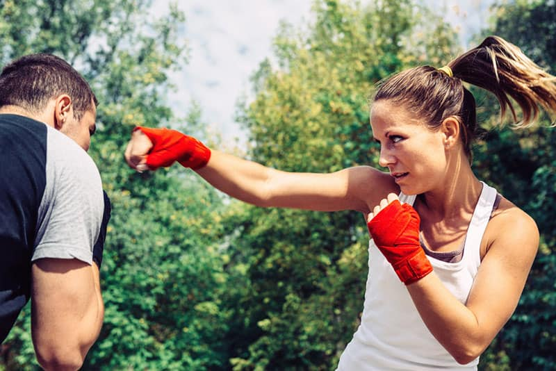 Woman throwing a punch to man on taebo training