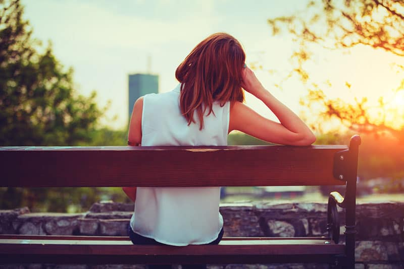 Girl enjoying city view from a bench in sunset / sunrise time.