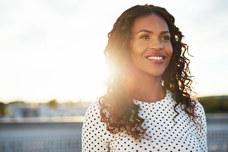 Happy confident young woman backlit by the morning sun standing on an urban rooftop looking into the distance with a lovely warm smile