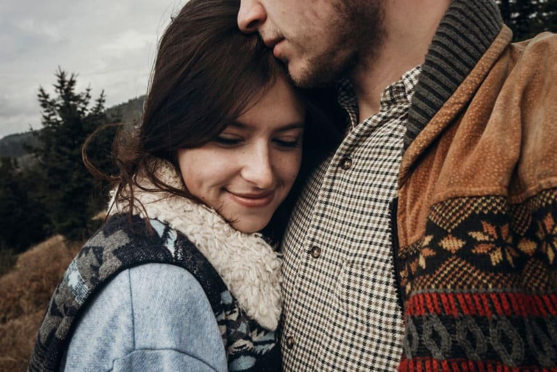 happy hipster traveler couple hugging on top of mountains. romantic moment of stylish family. wanderlust and travel concept with space for text