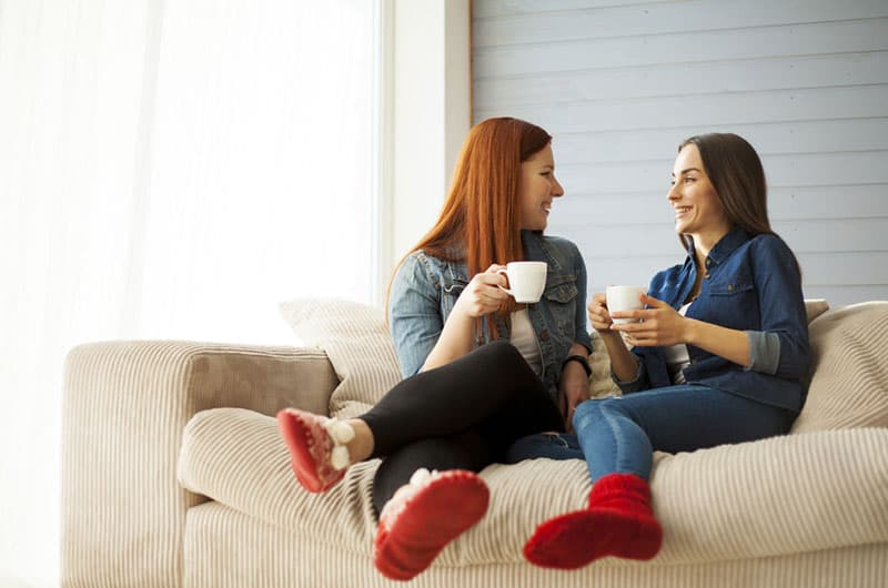 Two young beautiful cheerful girlfriends in blue jeans shirt sitting on sofa at home laughing and drinking coffee from a white cups. Girls in red socks.