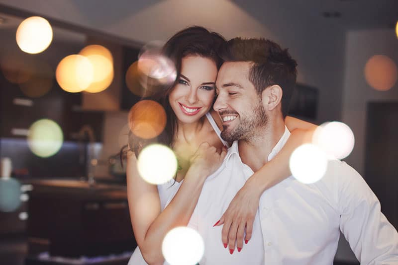 Young successful couple smiling, woman embrace man indoors, bokeh
