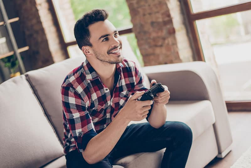 Portrait of attractive brunet hipster with bristle, holding joy stick and playing videogames on tv at vacation, sits at home on the cozy couch, successful, he is winning at crazy car race