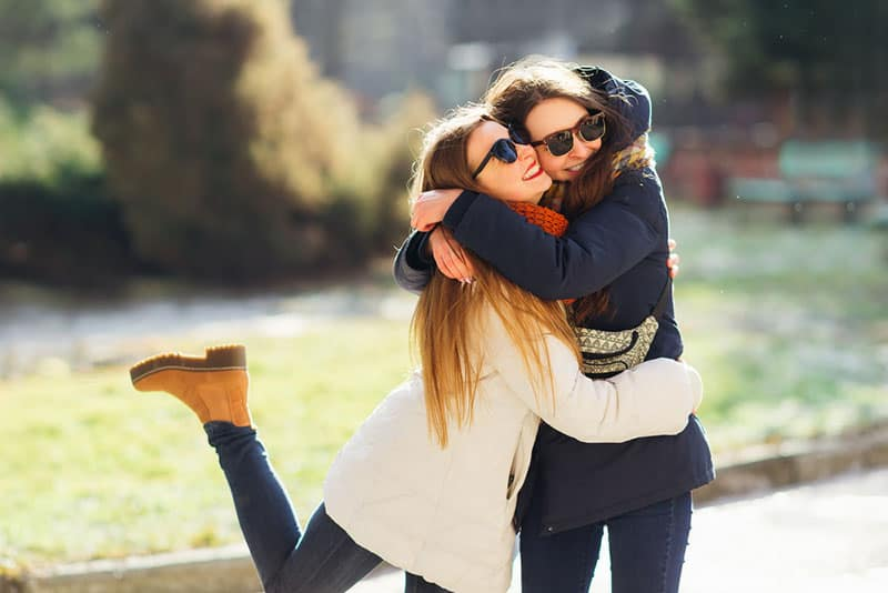 Young girl hugging her older sister smiling. Two long haired best friends having the best time of their lives.