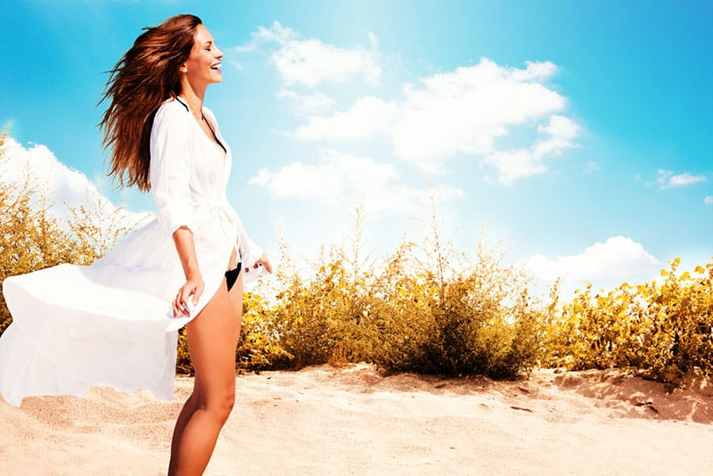 smiling woman in white dress and bikini standing on beach, sunny summer day