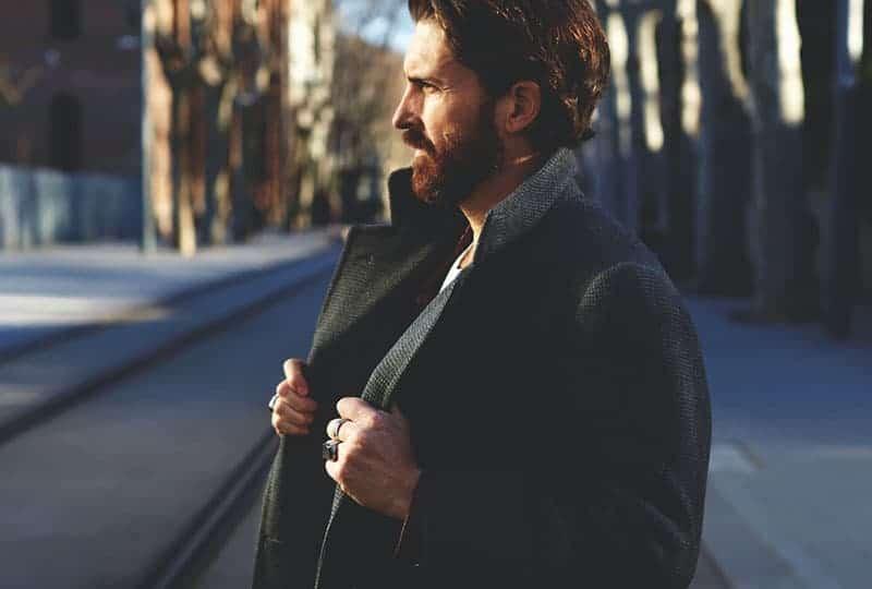 side view of man wearing black coat