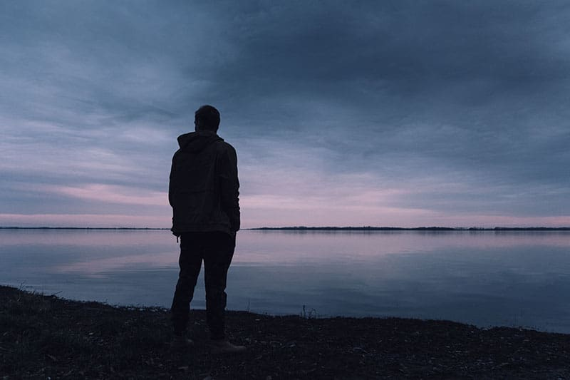 silhouette of man standing in front of water