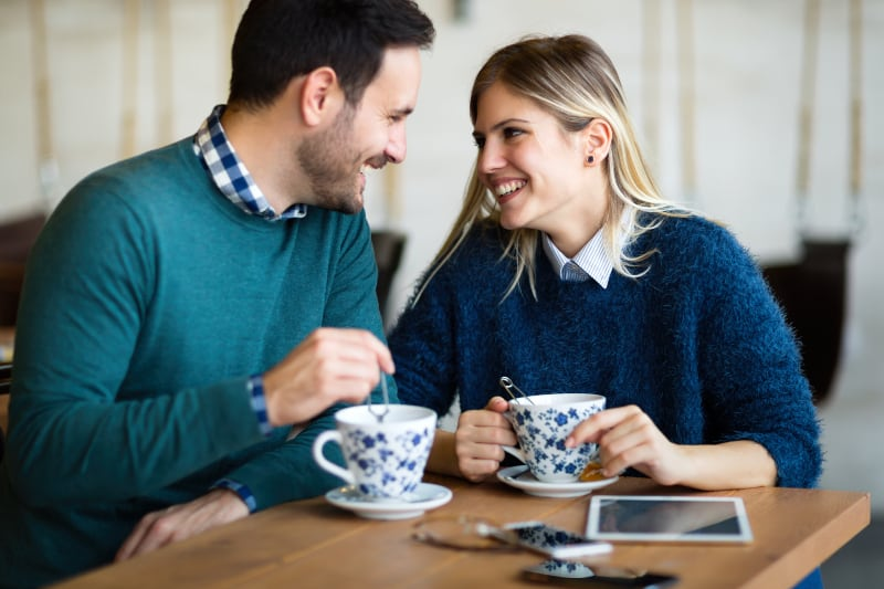 smiling couple looking each other in cafe