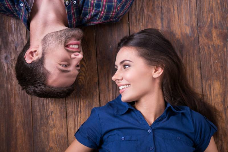 smiling couple lying together on the floor and looking at each other