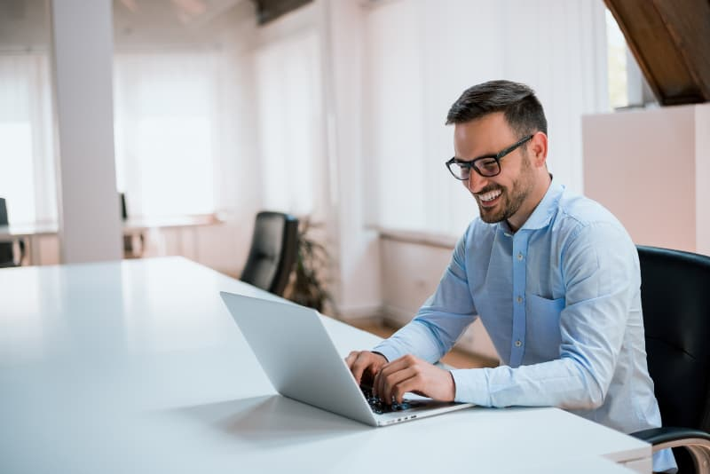 smiling man wearing blue shirt and typing on laptop in office