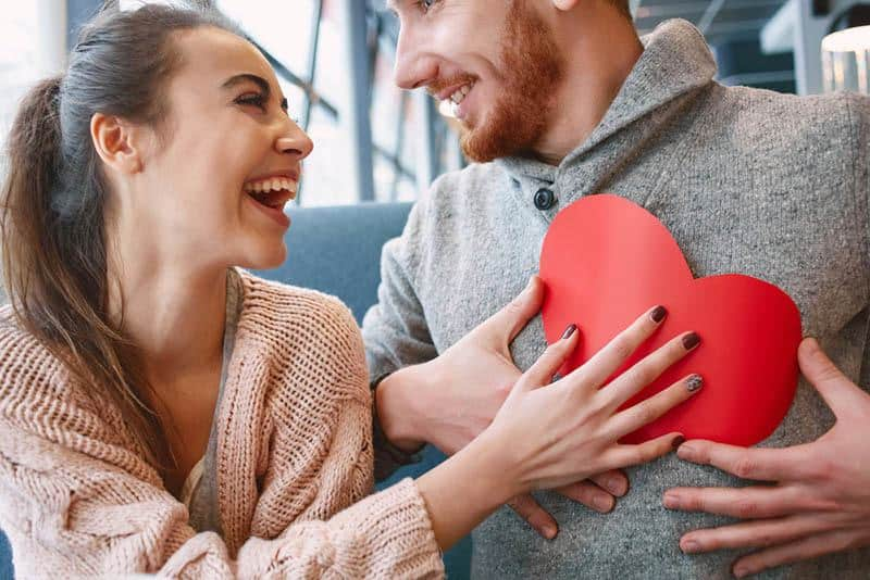smiling woman giving her man a paper shape of heart