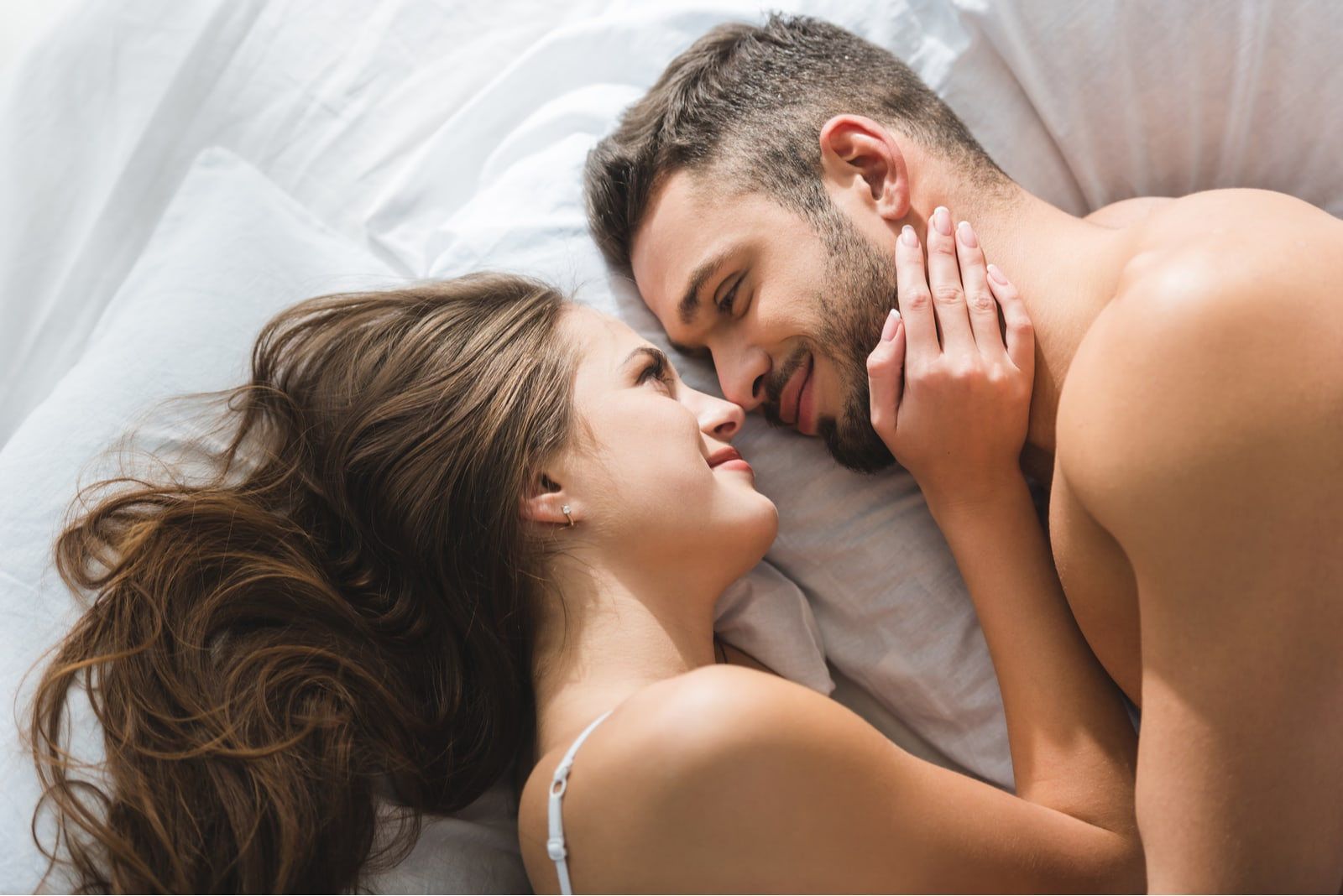 smiling young couple cuddling in bed in morning