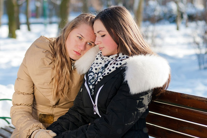 two friends hugging on the bench