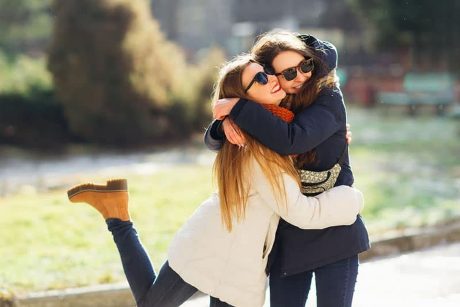 two friends with glasses and long jackets embracing