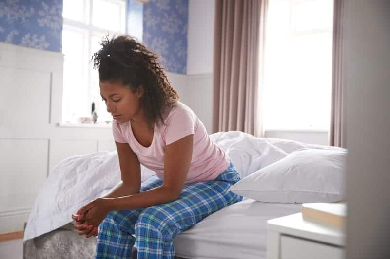 unhappy woman sitting on bed