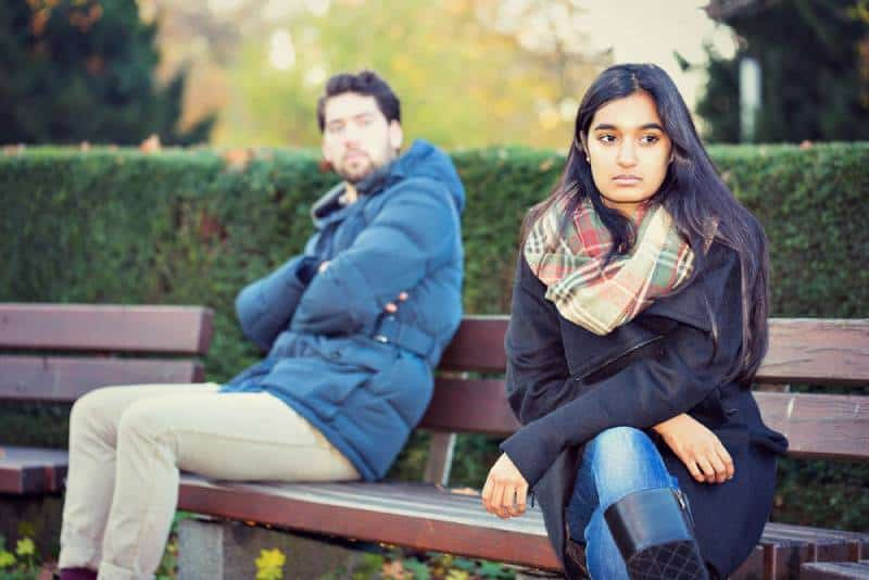 upset couple sitting on a park bench