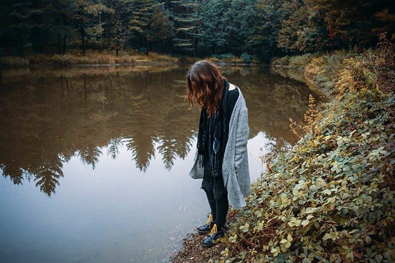 woman looks thoughtful near lake